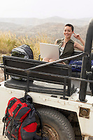 Woman using laptop sitting in back of four wheel drive car in desert portrait