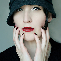 Close-up portrait of a young woman with pale skin and brown eyes, with a vintage hat and red lipstick staring at the camera.