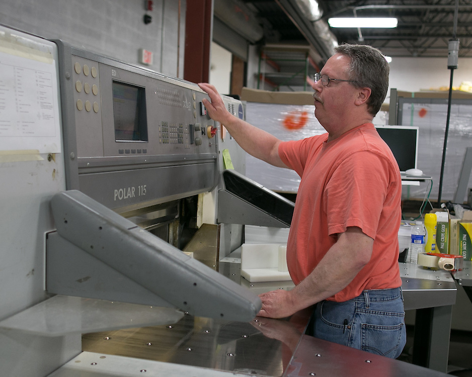 Bill Benedict cuts printed materials at Phoenix Graphics in Rochester on Thursday, April 9, 2015.