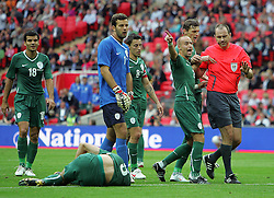 The ref is surrounded by Slovenian players after his penalty award during the international friendly match between England and Slovenia at Wembley Stadium, London on the 5th September 2009