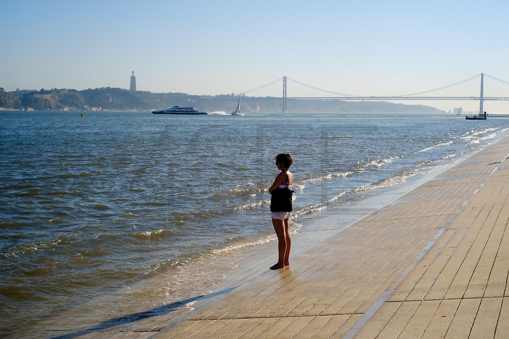 A lady by the Tagus riverside. Terreiro do Paço, the largest Lisbon square, and is one of the most well-know place to visit in Lisbon.