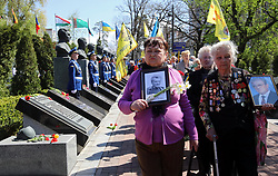 April 26, 2018 - Kyiv, Ukraine - Women carry photographs of the dead during a tribute-paying ceremony at the Memorial Complex 'Monument to the Victims of the Chornobyl Tragedy' on the 32nd anniversary since the accident at the fourth reactor of the Chornobyl (Chernobyl) Nuclear Power Plant in Kyiv, capital of Ukraine, April 26, 2018. Ukrinform. (Credit Image: © Tarasov/Ukrinform via ZUMA Wire)