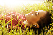 Girl laying in grass listening to music with earphones