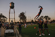"Cheerleaders for the Bakersfield High School football team practice before a game. The words ""Driller Country"" can be seen painted all over campus: a reference to the mascot, the Driller. Bakersfield High School is the only school in the area whose mascot reflects the oil culture of the region."