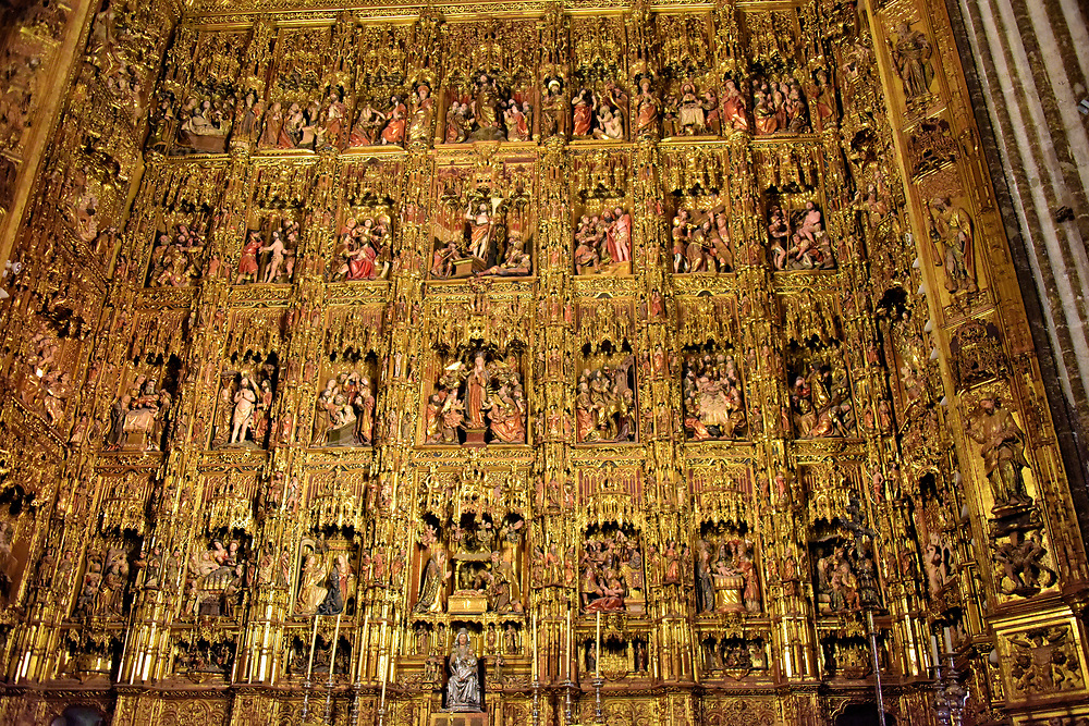 High Altar in Seville Cathedral in Seville, Spain<br /> The interior of Seville Cathedral is magnificent in every way. The crowning glory is the world&rsquo;s largest altarpiece. Craftsman Pierre Dancart spent 44 years carving Retablo Mayor from wood. The gilded high altar of Capilla Mayor (Grand Chapel) features scenes from the Old Testament, the life of Christ plus images of saints. At the bottom center is Santa Maria la Sede, the cathedral&rsquo;s patron saint.