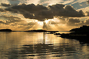 Intense golden sunset with numerous cclouds and crepuscular rays over a gently rippled calm Irish Sea at Trearddur Bay, Holy Island, Anglesey