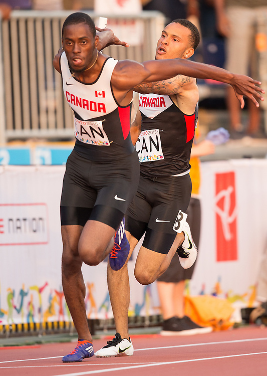 Brendan Rodney of Canada receives the button from Andre de Grasse during the men's 4X100 metre relay at the 2015 Pan American Games at CIBC Athletics Stadium in Toronto, Canada, July 25,  2015.  AFP PHOTO/GEOFF ROBINS