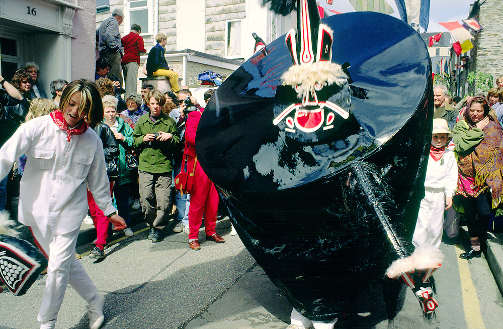 Padstow, Cornwall. A girl teaser leads the Hobby Horse through narrow streets during the annual May Day Hobby Horse festival.