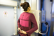 A young woman has a digital chest x-ray on the NHS Mobile X-ray Unit (MXU) van screening for tuberculosis (TB). The van is parked outside a hostel in central London and the visit is part of a public health intervention for Active Case Finding for TB in hard to reach groups. The rates of TB in London are higher than any other Western European capital and is a major public health problem. TB is an infectious disease, but treatable and curable if diagnosed in time. Early diagnosis is a key to TB control and Active Case Finding is an important part of this.