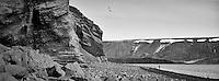 By lake Kleifarvatn at Reykjanes, Iceland. A person walking on the beach, seagull flying above. Rocks and sand in forground. Við Kleifarvatn á Reykjanesi. Manneskja á gangi við ströndina, sjófugl á flugi. Grjót og sandur í forgrunni.