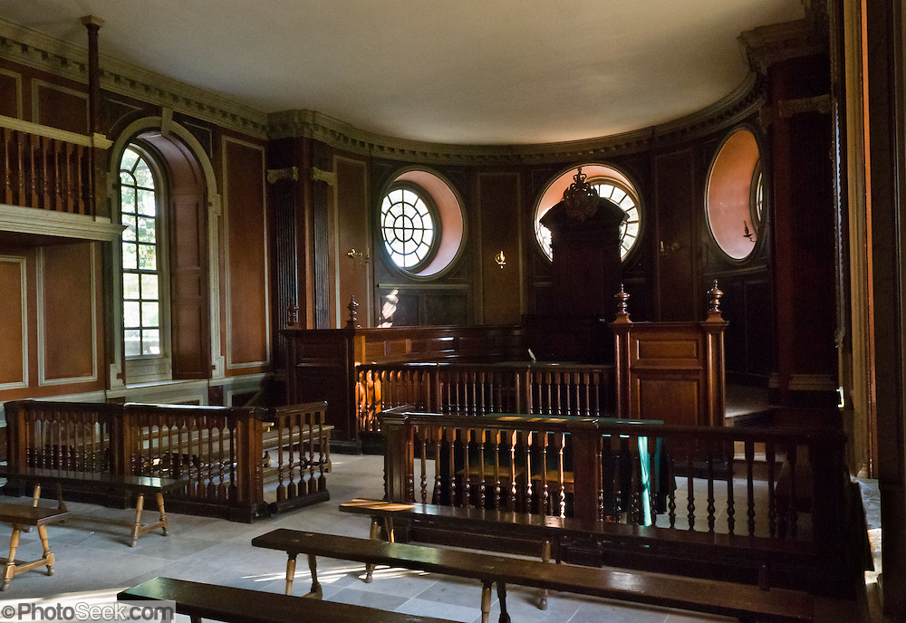 "The courtroom in the Capitol building at Colonial Williamsburg. The present Capitol was dedicated in 1934, designed by the architects Perry, Shaw & Hepburn as a recreation of the 1705 structure which was the first Capitol building in America. Colonial Williamsburg is the historic district of the city of Williamsburg, Virginia, which was colonial Virginia's capital from 1699 to 1780, and a center of education and culture. Here, Thomas Jefferson, Patrick Henry, James Monroe, James Madison, George Wythe, Peyton Randolph, and dozens more helped mold democracy in the Commonwealth of Virginia and the United States. Motto: ""that the future may learn from the past.""  Interpreters work, dress, and talk as they did in the era, teaching visitors. The 301-acre Historic Area is located immediately east of the College of William and Mary, which was founded at Middle Plantation in 1693. The new College, long a desire of the colonists, was a key factor in the establishment of the town as capital of Virginia in 1698 and its renaming for King William III of England shortly thereafter. Jamestown and Yorktown, the other two points of the Historic Triangle, are linked to Colonial Williamsburg by the National Park Service's bucolic Colonial Parkway."