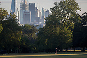With the skyline of the capital's financial district, the City of London in the distance, man looks into bright morning sunlight in Ruskin Park, on 10th August 2018, in London, England.