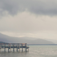 A dock on Lake Tahoe, early one summers morning as storm clouds roll in.