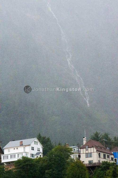 A waterfall cascades down a steep cliff behind houses in the city of Juneu, Alaska.