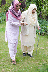 Young female carer and older woman walking in the garden,