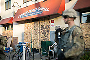 Members of the Minnesota National Guard keep watch over the Cedar Food and Grill in Minneapolis, Minnesota on Monday, June 1, 2020. The minority-owned grocery store was one of the few in the area that was not damaged or looted during the civil unrest in the last days of May in Minneapolis.