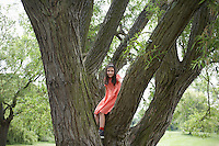 Girl (7-9) standing in tree portrait