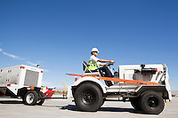 Young male ground crew driving truck at airport runway