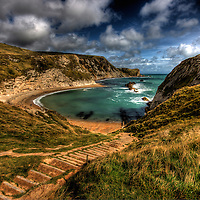 Uneven steps leading down in to Man of War bay in dorset looking out over a windy bay with white water breaking over some rocks.