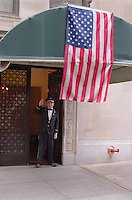 Park Avenue apartment building with doorman and US flag in upper Manhattan New York City.