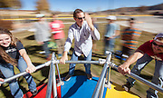 Dr. John Mason guides students in a physics lesson, using a playground-variety merry go round outside Kelley Hall.