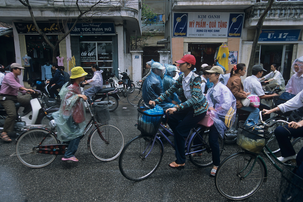 Asia, Vietnam, Hanoi, Chaotic traffic in city's Old Quarter as school lets out during rain shower