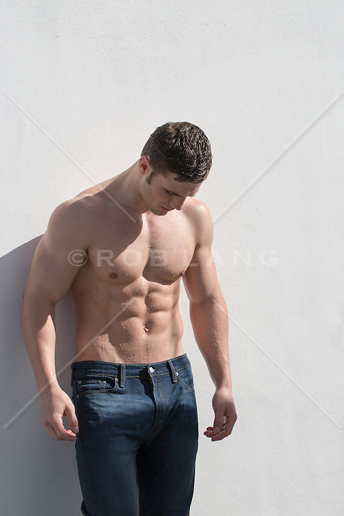 shirtless muscular man in jeans against a white wall outdoors