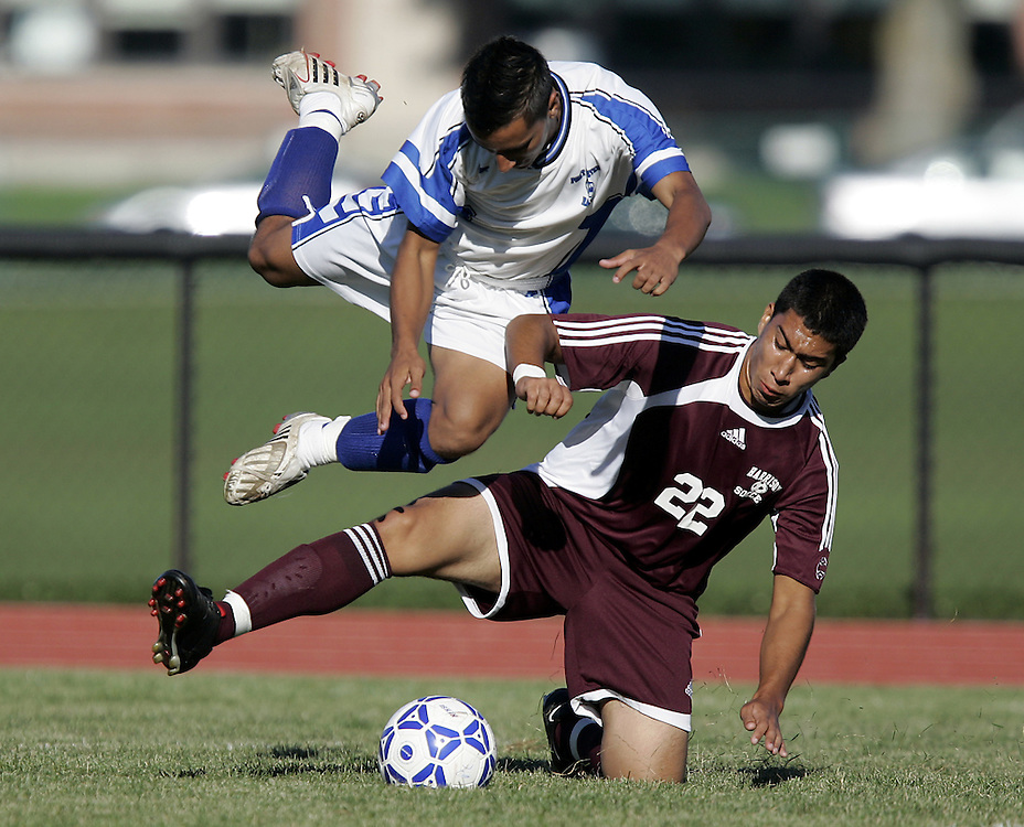 Port Chester, NY / 2008 - Port Chester's Juan O'Campo, left, goes airborne while Harrison's Antonio Britto gets to the ball during a high school boys soccer game between Port Chester and Harrison at Port Chester High School Sept. 18, 2008. Harrison won the game 2-1. ( Mike Roy / The Journal News )