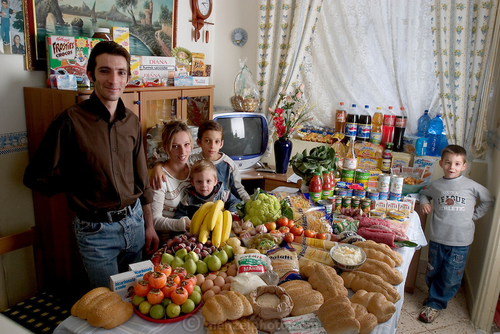 (MODEL RELEASED IMAGE. In the kitchen of their apartment in Palermo, Sicily, Italy, the Manzo family: Giuseppe, 31, Piera Marretta, 30, and their sons (left to right) Mauritio, 2, Pietro, 9, and Domenico, 7 stand and sit around a week's worth of food. Cooking methods: gas stove, microwave. Food preservation: refrigerator-freezer. Favorite foods? Giuseppe (who is a fishmonger): fish. Piera and Domenico: pasta with ragú (meat sauce). Pietro: hot dogs. Mauritio: frozen fish sticks. /// The Manzo family is one of the thirty families featured in the book Hungry Planet: What the World Eats (p. 174). Food expenditure for one week: $260.11 USD. (Please refer to Hungry Planet book p. 175 for the family's detailed food list.)