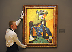 © Licensed to London News Pictures. 12/04/2012. London, UK . A Sotheby's employee holds Picasso's 'Femme assise dans un fauteuil' which is expected to fetch 20 - 30 million US dollars. Photocall for Sotheby's Impressionist and Modern Art Evening Sale 12 April 2012. Photo credit : Stephen Simpson/LNP