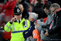 A policeman speaks with West Bromwich Albion manager Alan Pardew before the match during the Emirates FA Cup, fourth round match at Anfield, Liverpool.