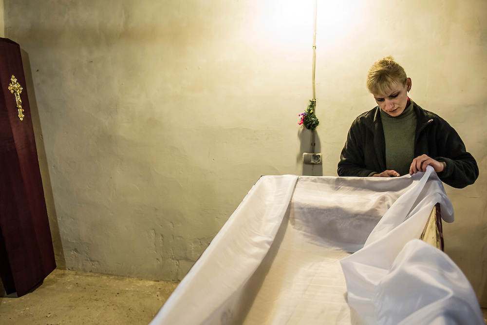 DONETSK, UKRAINE - FEBRUARY 3, 2015: Lyudmila Levochko builds a casket in Donetsk, Ukraine. The city government provides basic but free or low-cost caskets for victims of shelling or others who are no longer able to afford funeral expenses, the demand for which has increased significantly in past weeks as violence has flared once again. CREDIT: Brendan Hoffman for The New York Times