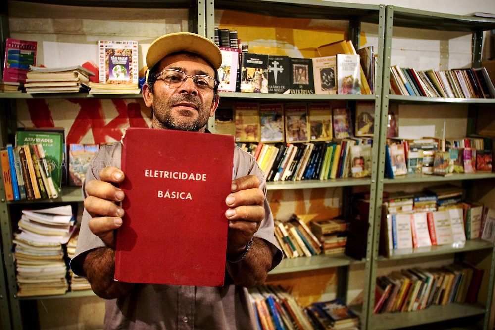 Severino, resident and co-founder of the Prestes Maia Library, shows a book about basic electricity. He was the responsible person from the maintenance of the building electricity. He didn't know to read.