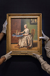 """© Licensed to London News Pictures. 01/07/2016. London, UK.  Technicians prepare to hang """"A Dutch Girl at Breakfast"""" by Jean-Etienne Liotard (est. GBP 4-6 million), at the preview of Sotheby's London Old Masters evening sale which takes place 6 July.   Photo credit : Stephen Chung/LNP"""