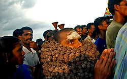 "A Hindu pilgrim worshipping Lord Shiva and the God of the Sea joins hundreds of fishing families from New beach in Nagapattinum district in Tamil Nadu, India as they take part in the unique ritual of reliving the day when Athi Baktha Nayanar found a gold fish in the ocean, offered it to his God and received ""moksha"", September 2,2005. Villagers worship this God who is know to be the God of the Sea and the 49th nayanmar. The yearly ritual symbolizes an unwavering  pious man who always offered his daily catch to his God first, even when people in his village were starving. The ritual had been stopped for 25 years and many fishermen believed this is why the tsunami ravaged the coast of India.  (Ami Vitale)"