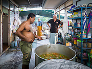 10 JULY 2015 - BANGKOK, THAILAND:  A man makes chicken curry for Iftar at Haroon Mosque in Bangkok. Iftar is the evening meal when Muslims end their daily Ramadan fast at sunset. Iftar is a communal event at Haroon Mosque and hundreds of people usually attend the meal.    PHOTO BY JACK KURTZ