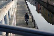 Cyclist along Naviglio Grande (canal) towpath in Milan, January 20, 2011. Towpath originally used as a pathway for horses towing barges back to Ticino river. In the picture the towpath run under the roadbridge of Valenza street at Ticinese district. © Carlo Cerchioli..Ciclista lungo l'Alzaia del Naviglio Grande a Milano, gennaio 2011. L'Alzaia originariamente era percorsa dai cavalli che trainavano le chiatte vuote verso il Ticino. Nella foto l'Alzaia corre sotto il ponte stradale di via Valenza al quartiere Ticinese.