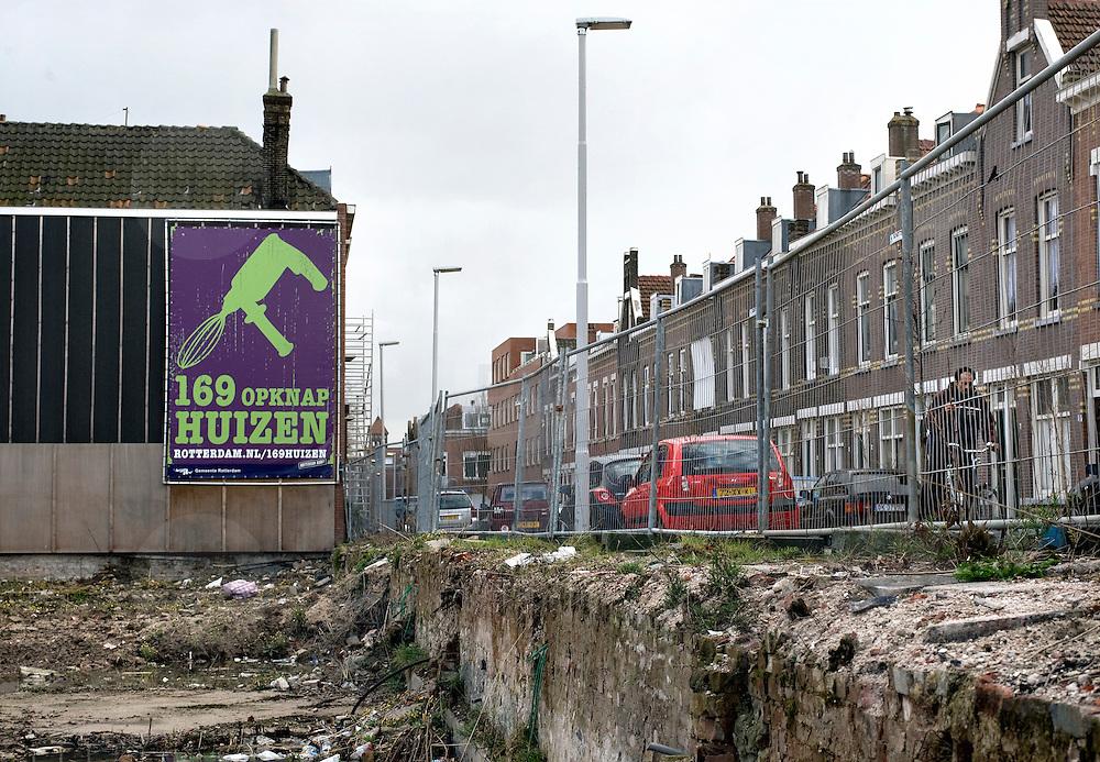 Nederland Rotterdam 17 maart 2008 20080317..Braakliggend terrein met op achtergrond opknaphuizen aan de Beukelaarstraat in achterstandswijk Riederbuurt. Met dit initiatief, 169 opknaphuizen, wil de gemeente het opknappen van oudere woningen en de betrokkenheid van Rotterdammers bij hun woning én hun buurt stimuleren. Het gaat om panden in Rotterdam west en zuid die de afgelopen jaren zijn aangekocht door de gemeente omdat zij niet goed werden onderhouden. De woningen worden aangeboden tegen een sterk gereduceerde prijs. Hier tegenover staat dat kopers zich verplichten tot het volledig opknappen en zelf bewonen van deze woningen...169 opknaphuizen Uniek verkoopproject van start.Vanaf 16 mei 2007 heeft de gemeente Rotterdam op Zuid en in Spangen 169 opknaphuizen te koop. Het gaat om panden die zijn aangekocht omdat ze de afgelopen jaren werden verwaarloosd. Voor kopers geldt de verplichting de woning van buiten en binnen op te knappen. Genteresseerden kunnen voor meer informatie de website www.rotterdam.nl/169huizen bezoeken.  ??Het ministerie van VROM ondersteunt dit voor Nederland unieke project met een stevige subsidie. Hierdoor kunnen de aangekochte woningen tegen een sterk gereduceerde prijs worden verkocht. Een woning met twee verdiepingen kost gemiddeld 40.000 euro en voor ongeveer 75.000 euro is een pand met vier woonlagen te koop. De kosten van de verbouwing komen daar voor de koper nog bij. Drie banken hebben hun medewerking aan dit project toegezegd (ABNAMRO, Fortis, Rabobank). Daar kunnen kopers terecht voor het afsluiten van een hypotheek. Een coach van Steunpunt Wonen staat de kopers bij. ??Karakteristieke panden ?De opknaphuizen zijn gebouwd in de jaren twintig en dertig van de vorige eeuw. De bouwkundige staat is goed, evenals de funderingen. Het zijn vaak karakteristieke panden met bijzondere details. De huizen maken deel uit van bouwblokken die - met hulp van de gemeente - als geheel worden opgeknapt. ??De aangekochte ruimte mag alleen gebruikt worde