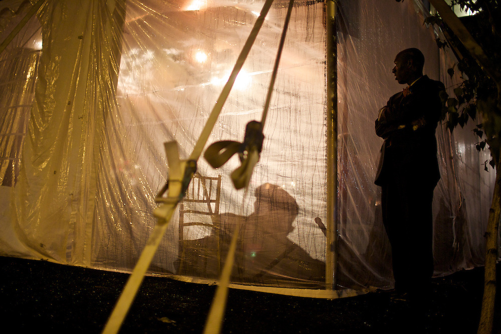 An employee at an afterhours party stands outside the tent the night before the 2012 Democratic National Convention in Charlotte, N.C. on Sept. 3, 2012.  Photo by Greg Kahn