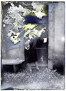 severely eroding glass plate of woman standing by front door of her house