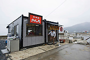 A customer leaves a temporary noodle restaurant at Kyubun-hama, Ishinomaki,  Miyagi Prefecture on Feb. 24 2012. .Photographer: Robert GilhoolyView from Jodo-ji temple over Rikuzentaka, Iwate Prefecture, Japan on 29 Feb. 2012. .Photographer: Robert Gilhooly