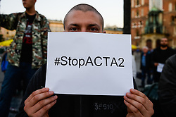 October 5, 2018 - Krakow, Poland - A protester seen holding a poster saying, STOP ACTA 2.0 during the demonstration..Protest against the implemented EU Copyright Directive (known as ACTA 2.0) in front of Adam Mickiewicz Monument at the Main Square. On September 12, 2018 an updated version of the controversial articles 11 and 13 of the Directive on Copyright in the Digital Single Market were approved by the European Parliament. EU claims that article 11 and 13 aim to protect the copyrights and to bring profits to news outlets, artists and others when social media platforms such as Google, Facebook and others link their work. (Credit Image: © Omar Marques/SOPA Images via ZUMA Wire)