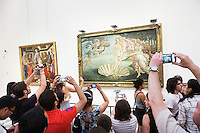 "FLORENCE, ITALY - 29 JUNE 2016: Visitors photograph the ""Birth of Venus"" (1484) by Sandro Botticelli, in the Botticelli room of the Uffizi Gallery in Florence, Italy, on June 29th 2016.<br /> <br /> Art historian Eike Schmidt, former curator and head of the Department of Sculpture, Applied Art and Textiles at the Minneapolis Institute of Arts, became the first non-Italian director of the Uffizi in August 2015, replacing Antonio Natali who directed the gallery for 9 years. One of the main goals of the new director is to open the Vasari Corridor to the general public. Currently the corridor can only be visited with group reservations made by external tour and travel agencies throughout the year.<br /> <br /> The Vasari Corridor is is a 1-kilometer-long (more than half mile) elevated enclosed passageway which connects the Palazzo Vecchio with the Palazzo Pitti, passing through the Uffizi Gallery and crossing the Ponte Vecchio above the Arno River, in Florence. The passageway was designed and built in 1564 by Giorgio Vasari in only 6 months to allow Cosimo de' Medici and other Florentine elite to walk safely through the city, from the seat of power in Palazzo Vecchio to their private residence, Palazzo Pitti. The passageway contains over 1000 paintings, dating from the 17th and 18th centuries, including the largest and very important collection of self-portraits by some of the most famous masters of painting from the 16th to the 20th century, including Filippo Lippi, Rembrandt, Velazquez, Delacroix and Ensor."