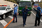 Protestors, mostly elderly people. in front of the gates of Camp Schwab, try to block trucks carrying construction vehicles onto the base. They assert construction can still be stopped. <br /> The police systematically remove protestors, often by carrying them, away from the gates.<br /> <br /> Protestors, outside the US Marine Corps Camp Schwab base, rally against the expansion of the facility. New construction will double the size of the current base, creating a US military mega-base that will include two airstrips. Plans are afoot to reclaim land in the surrounding sea to achieve this. Preparations for construction has already started but demonstrators assert construction can still be stopped.<br /> <br /> USMC Camp Schwab. Named after Battle of Okinawa hero, Albert E. Schwab, and built upon a former civilian internment camp, the remains of approximately 300 Okinawans still lie within the base. During the Cold War, the installation and its adjacent arsenal, stored nuclear warheads and, veterans say, a large cache of Agent Orange. Today live fire training and sea drills are held here. The proposed site for operations relocated from MCAS Futenma, the USMC envisages a new base with twin runways and a deepwater port. The Japanese government contends the environmental impact will be minimal but many Okinawans - Governor Takeshi Onaga included - argue that the millions of tons of landfill will cause irrevocable damage to the sea.<br /> <br /> Size: 20.6 sq km   Japanese base workers: 242