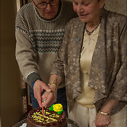 Married couple  celebrating their 50th Anniversary by cutting the cake