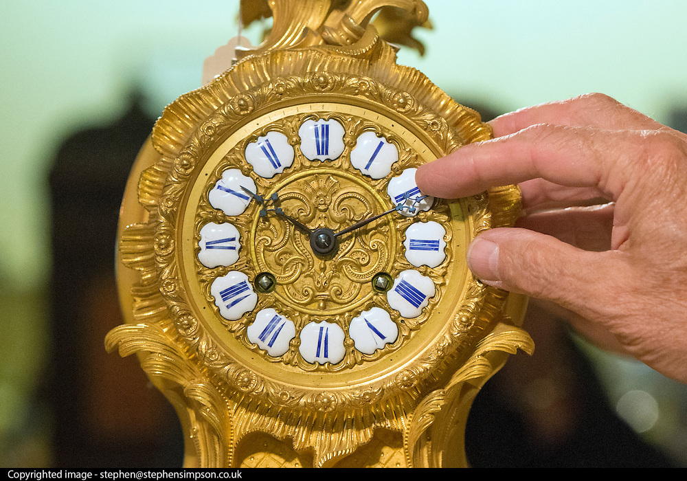 """© Licensed to London News Pictures. 23/10/2014. Guildford, UK. Michael Tooke changes mantlepiece clock in the shop. As British Summer Time comes to an end, staff at Horological Workshops start the task of changing the 100's of clocks at their store in Guildford, Surrey, UK. Michael Tooke who has owned the store for over 40 years and worked in the clock business all his life said. """"at this time of year we get a lot of people who bring clocks in for repair after they have changed the time incorrectly by winding back the hands manually"""". Clocks change on Sunday morning 26th October. Photo credit : Stephen Simpson/LNP"""