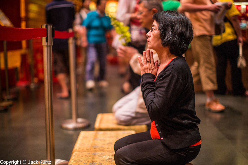 "16 DECEMBER 2012 - SINGAPORE, SINGAPORE:  A woman prays at the Buddha Tooth Relic Temple and Museum in the Chinatown section of Singapore. The temple houses a sacred Buddha tooth relic. It is a ""Mahayana"" Buddhist temple, the larger of the two Buddhist sects. Mahayana Buddhism is practiced in India, China, Vietnam (northern), Japan, Tibet, Mongolia, Korea and in Chinese immigrant communities around the world.      PHOTO BY JACK KURTZ"
