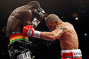 June 13, 2009; New York, NY, USA;  WBO Welterweight Champion Miguel Cotto (red/gray) and challenger Joshua Clottey (black) trade punches during their 12 round bout at Madison Square Garden.
