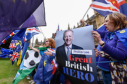 © Licensed to London News Pictures. 12/06/2018. LONDON, UK.  Anti-Brexit protesters hold up posters of Phillip Lee outside the Houses of Parliament as MPs begin two days of debate to vote on amendments to the EU Withdrawal Bill. Justice Minister Phillip Lee resigned today in protest about the economic impact of Brexit.   Photo credit: Stephen Chung/LNP
