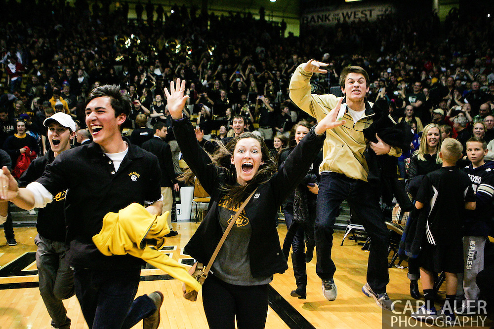 December 7th, 2013:  Colorado Students storm the court after Colorado Buffaloes junior guard Askia Booker (0) hits a three point shot from near mid court to beat the #6 Kansas Jayhawks 75-72 in the NCAA Basketball game between the Kansas Jayhawks and the University of Colorado Buffaloes at the Coors Events Center in Boulder, Colorado